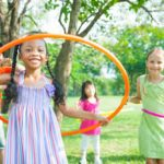 Group of children playing with hula-hoops outdoors in summer