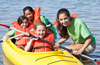 Yoith leader teaching young children to kayak