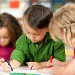 Young children coloring or writing in school classroom