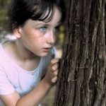 Young girl hiding behind tree isolated from classmates or friends