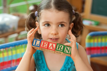 "Little girl holding up toy blocks that spell ""LEARN""."