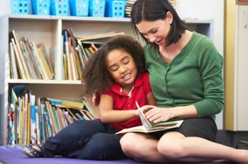 Teacher reading with student on floor mat
