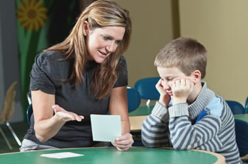 Teacher working closely with young student