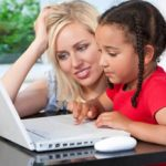 Tutor helping her young student learning on computer