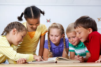 Five students gathered around a school book