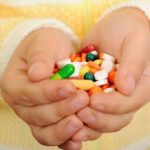 Child's hands filled with various medications
