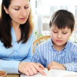 Mother helping her son with homework assignment