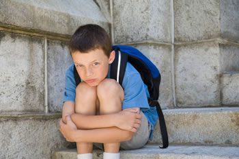 Young boy sitting alone holding his knees