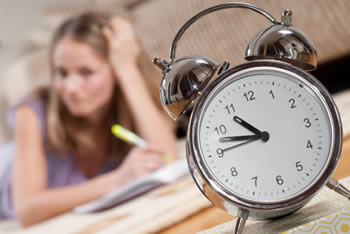 Student doing homework with clock