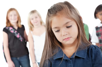Young girl standing apart from her peers
