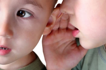 Young boy listening to a friend talking into his hear, demonstrating symptoms of Auditory Processing Disorder.