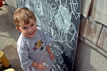Little boy writing with squiggles on chalkboard.