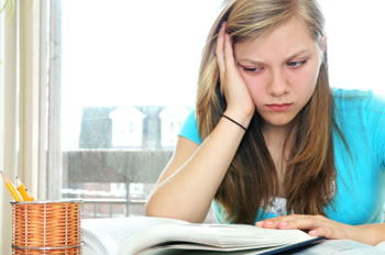 Young female student expressing frustration while rereading, demonstrating symptoms of Dyslexia.