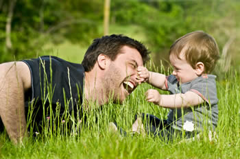 Father playing with his infant son in the tall grass