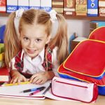 Little girl with backpack, books and school supplies