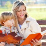 Mother reading a book to her son in the park