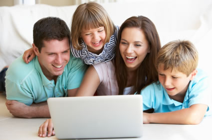 Happy family of four looking at laptop computer
