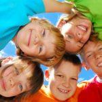 Smiling, huddled group of various aged children.