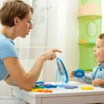 Mother working with letter toys and sounds with young son.