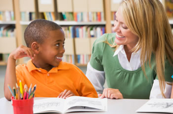 Teacher working with young student on reading skills