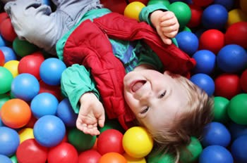 Young child playing in children's ball pit.