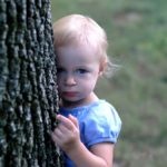 Little girl standing behind a tree