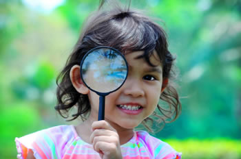 Little girl looking through a magnifying glass.