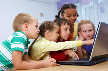 Young students gathered around a computer
